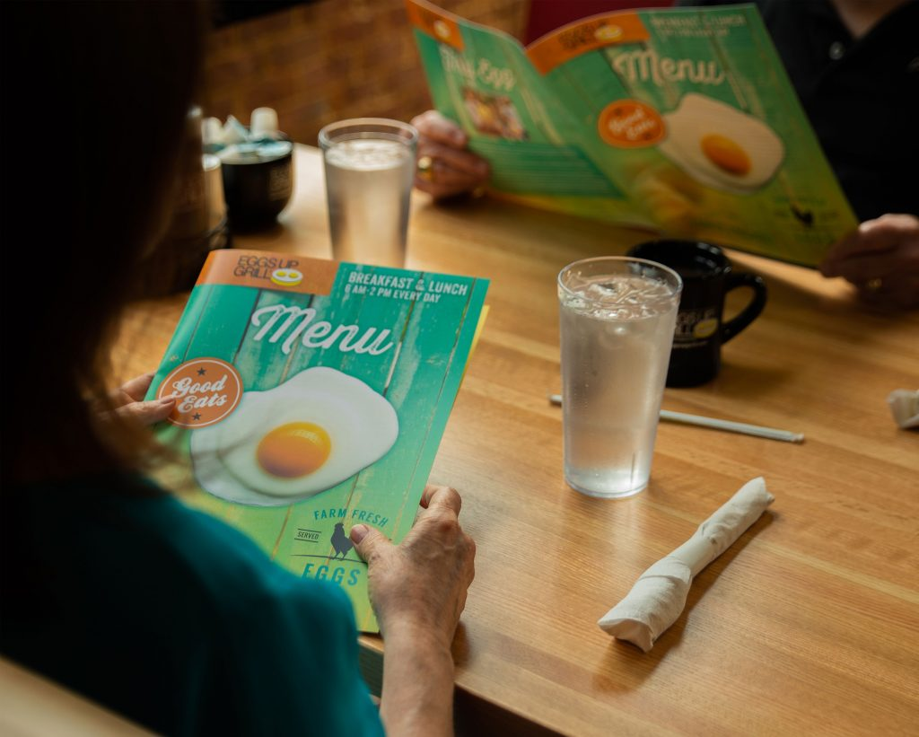 Image of diners with menus at Eggs Up Grill